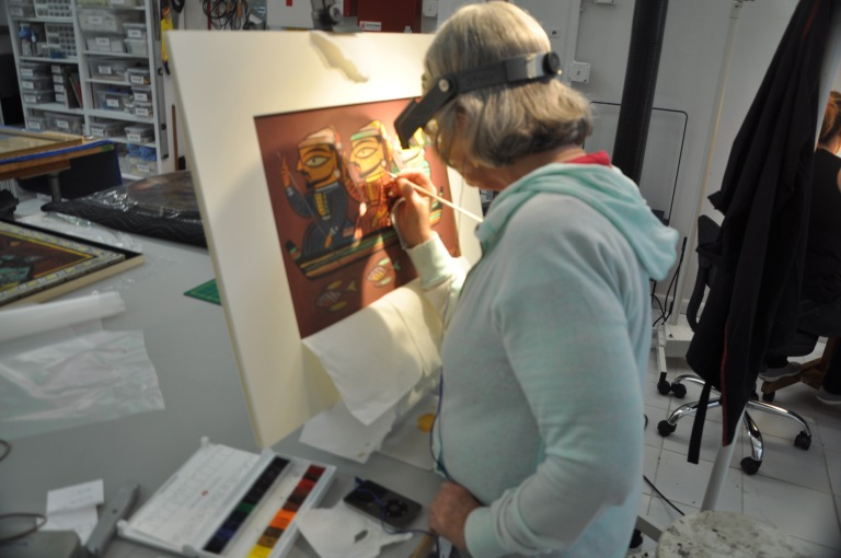 Conservator Rustin Levenson working on The World of Kantha. Photo courtesy of ArtCare.